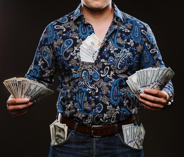 Un uomo che tiene un sacco di soldi banconote da 100 dollari in diverse tasche