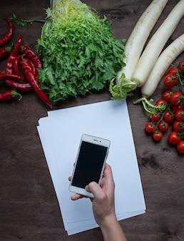 Un uomo che tiene uno smartphone in mano sul tavolo della cucina su una con verdure fresche. disteso.