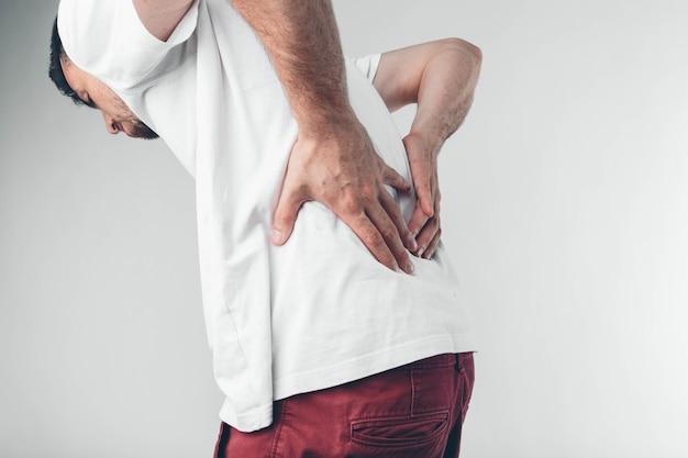 Un uomo che trattiene la schiena a causa del dolore