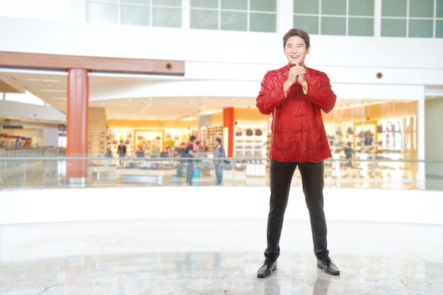 Un uomo cinese asiatico in un abito cheongsam con gesto di congratulazioni