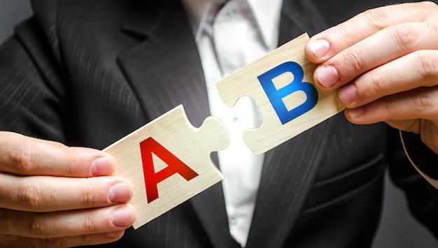 Un uomo collega i puzzle con le lettere a e b. metodo di ricerca di marketing di prova a / b