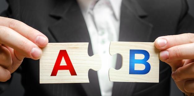Un uomo collega i puzzle con le lettere a e b. metodo di ricerca di marketing di prova a / b.