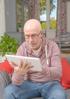 Un uomo con gli occhiali guardando un tablet