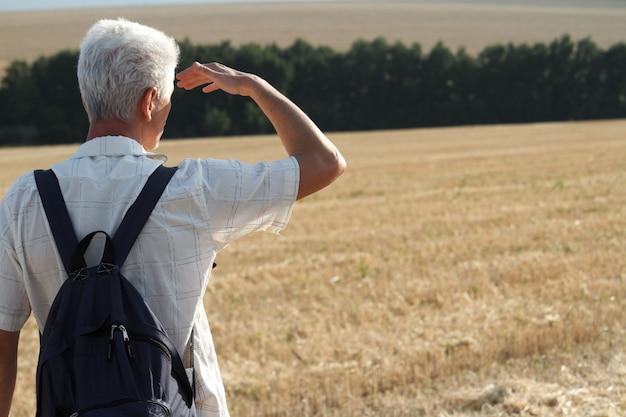 Un uomo con i capelli grigi e uno zaino nero dietro la schiena