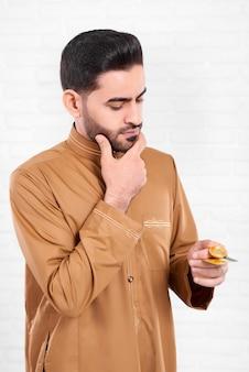 Un uomo con il nero sente, indossa una lunga camicia beige con il modello preciso