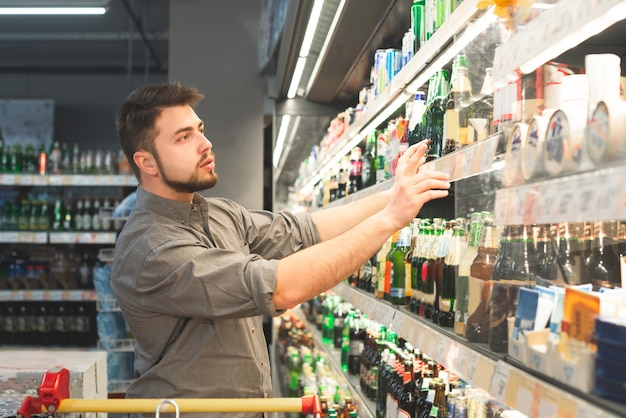 Un uomo con la barba che indossa una maglietta compra una birra nel reparto alcolici di un supermercato.
