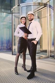Un uomo con la barba e una donna in abiti d'affari sta studiando disegni e documenti per un nuovo progetto