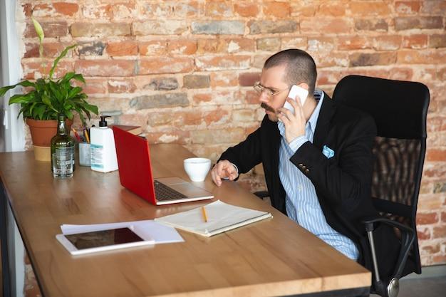 Un uomo con la barba in giacca e senza pantaloni lavora a casa da solo. ufficio a casa