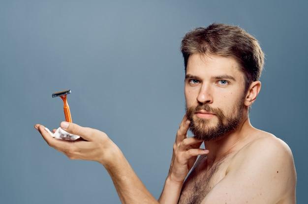 Un uomo con la barba tiene in mano un rasoio, procedure di bellezza, barbiere a casa