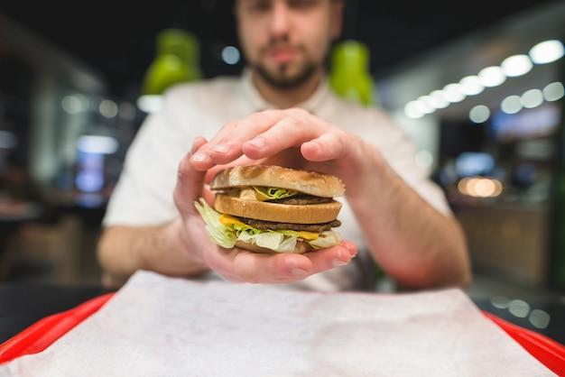 Un uomo con la barba tiene tra le mani un ottimo hamburger appetitoso. concentrati sull'hamburger. concetto di fast food.
