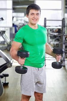 Un uomo con manubri facendo esercizi in palestra