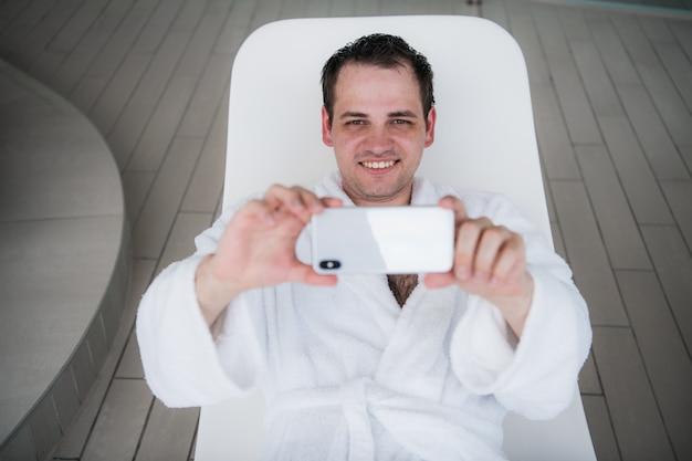 Un uomo con un accappatoio bianco giace a bordo piscina su una sedia a sdraio e guarda il nuovo costoso cellulare