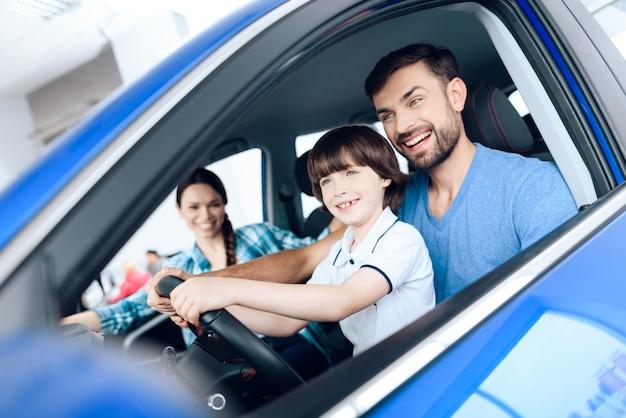 Un uomo con un bambino in braccio in posa in una nuova auto.