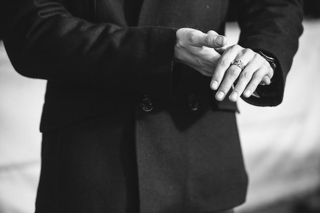 Un uomo con un cappotto con una sciarpa pone in strada per pubblicizzare l'abbigliamento maschile.