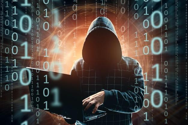 Un uomo con un cappuccio, un hacker, un attacco di hacker, una sagoma di un uomo, tiene in mano un computer portatile, minaccia