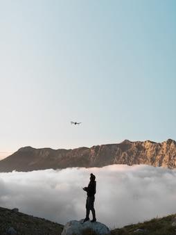Un uomo con un drone in montagna che vola dietro le nuvole