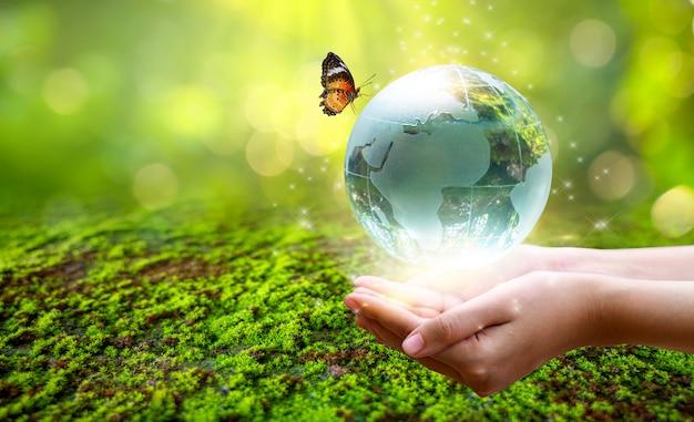 Un uomo con un globo di vetro concetto giornata terra salvare il mondo salvare l'ambiente il mondo è nell'erba dello sfondo verde bokeh