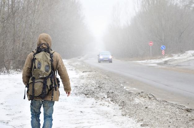 Un uomo con un grande zaino cammina lungo una strada asfaltata suburbana