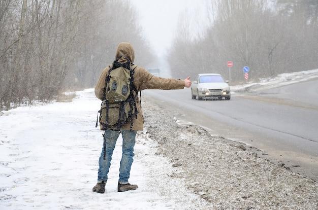 Un uomo con un grande zaino che mostra il pollice in alto per l'autostop