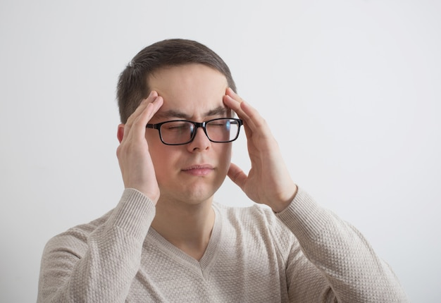 Un uomo con un mal di testa su sfondo un muro bianco