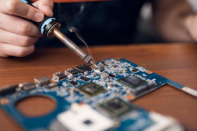 Un uomo con un saldatore ripara le apparecchiature informatiche.