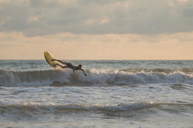 Un uomo con un surf tra le mani in riva al mare