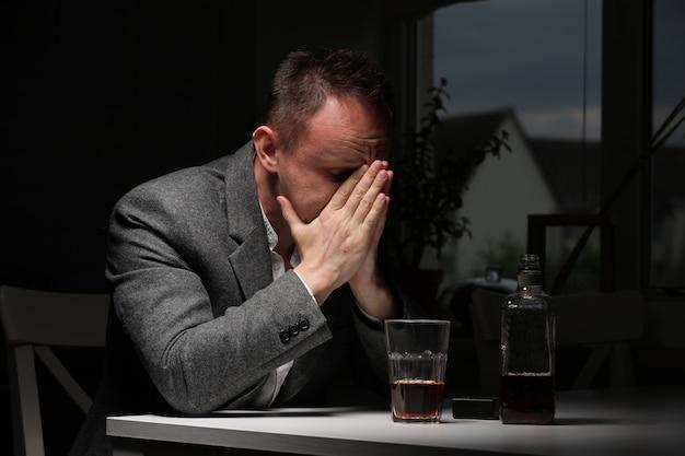 Un uomo con una bottiglia di whisky in cucina. il concetto di ubriachezza e alcolismo. padre alcolista. un uomo malato stanco nel dolore beve da solo. esperienza emotiva. messa a fuoco selettiva