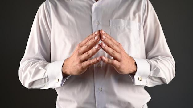 Un uomo con una camicia bianca esprime aiuto con le sue mani.