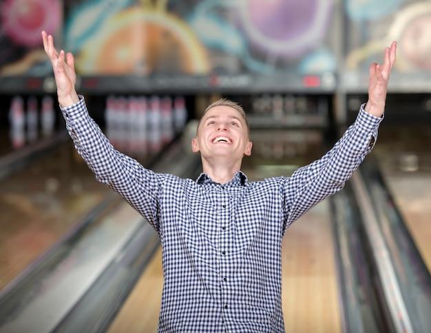 Un uomo con una maglietta alza le mani in un club di bowling.