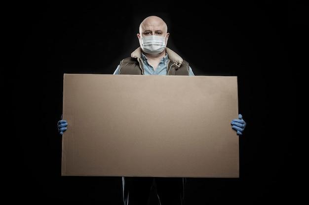 Un uomo con una maschera e guanti con una grande scatola di cartone in mano. consegna durante il periodo di quarantena della pandemia di coronavirus. sicurezza e precauzioni sfondo nero.