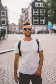 Un uomo con uno zaino cammina per le strade di amsterdam.