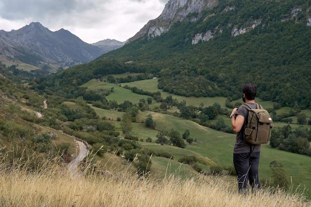 Un uomo con uno zaino in montagna. una strada molto lunga in lontananza.