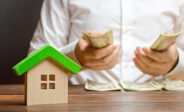 Un uomo conta soldi sulle figure della casa. calcolo della tassa di proprietà