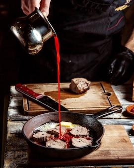 Un uomo cucina carne fritta in padella e versa il succo di pomodoro