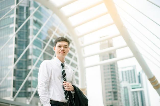 Un uomo d'affari asiatico sta andando a lavorare. è nell'ora di punta. il suo ufficio è nella città di bangkok.