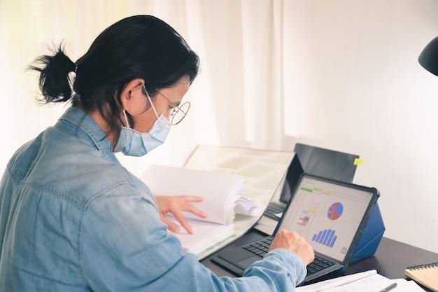 Un uomo d'affari che lavora con documenti e tablet digitale sul tavolo dell'ufficio a casa redige un rapporto sulle attività di avvio dopo che l'epidemia di coronavirus ha avuto un impatto sulle piccole imprese