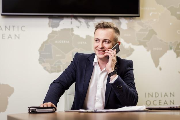Un uomo d'affari che parla su un telefono cellulare, uomo d'affari che parla al telefono in ufficio, uomo d'affari senior, ritratto di uomo d'affari che parla sul telefono cellulare, concetto di affari