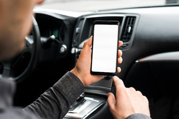 Un uomo d'affari che si siede nell'automobile facendo uso del telefono cellulare con lo schermo di visualizzazione bianco