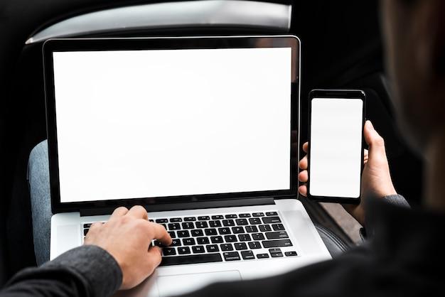 Un uomo d'affari con laptop e telefono cellulare con schermo bianco vuoto