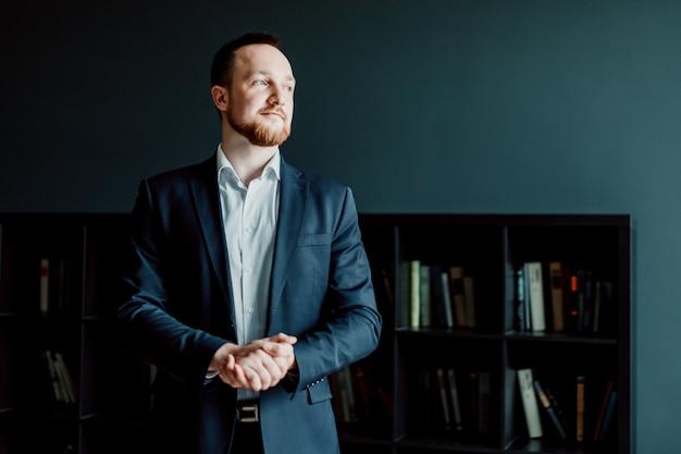Un uomo d'affari di successo e adulto in giacca e cravatta si trova in ufficio.