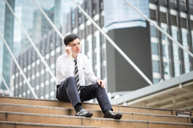 Un uomo d'affari è seduto alle scale e pensa a qualcosa.