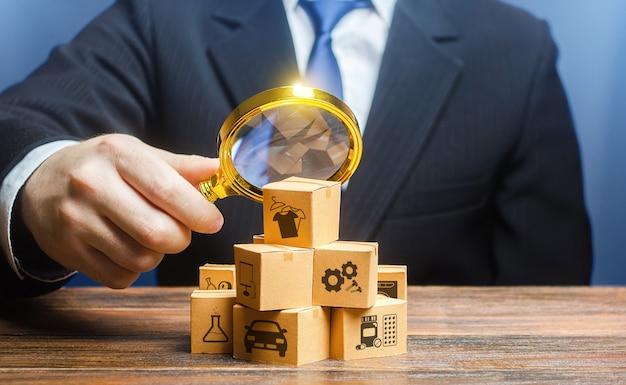 Un uomo d'affari esamina le merci delle scatole con la lente d'ingrandimento.