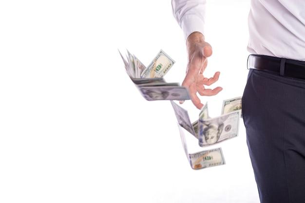 Un uomo d'affari estrae un batuffolo di dollari americani dalla tasca dei pantaloni e le bollette sono sparse in diverse direzioni in primo piano