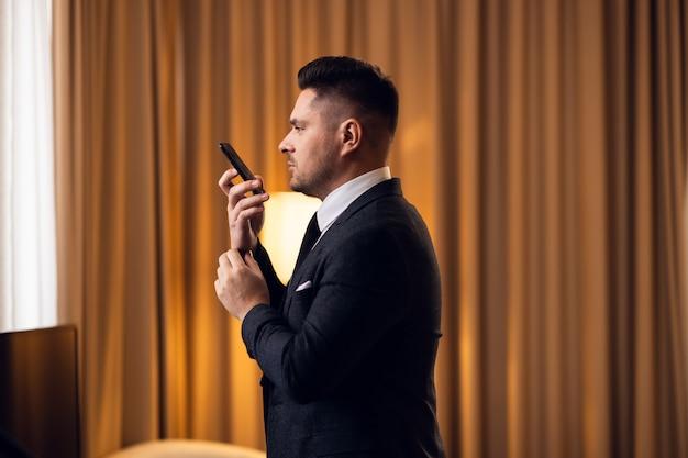 Un uomo d'affari impegnato a parlare al telefono, mentre si aggiusta i polsini in una stanza d'albergo.