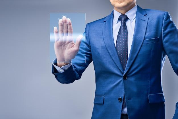 Un uomo d'affari in abito blu mette la mano su un pannello di accesso virtuale
