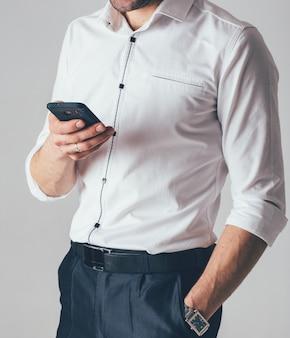 Un uomo d'affari in camicia bianca e pantaloni neri tiene in mano un telefono in ufficio. un uomo indossa un orologio da polso con la mano sinistra