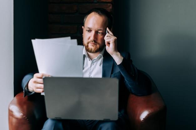 Un uomo d'affari in giacca e cravatta si siede su una sedia con un computer portatile e analizza le statistiche di borsa.