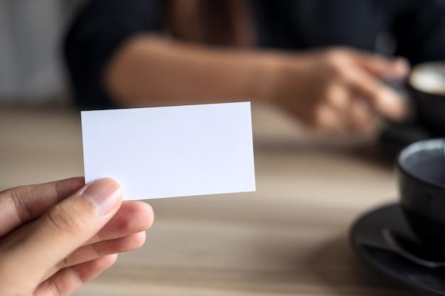 Un uomo d'affari in possesso di un biglietto vuoto con imprenditrice in background