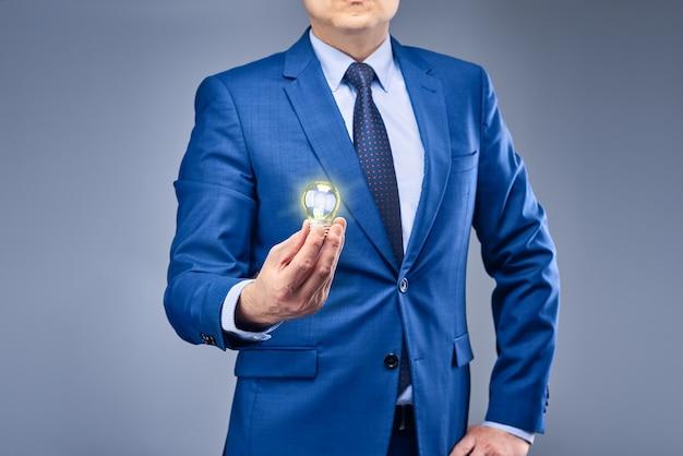 Un uomo d'affari in un abito blu detiene una lampadina gialla