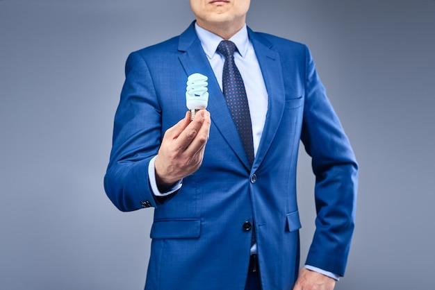 Un uomo d'affari in un abito blu detiene una lampadina